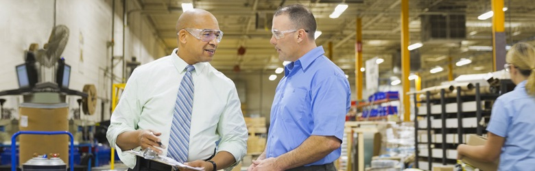 Two men discussing safety in a factory