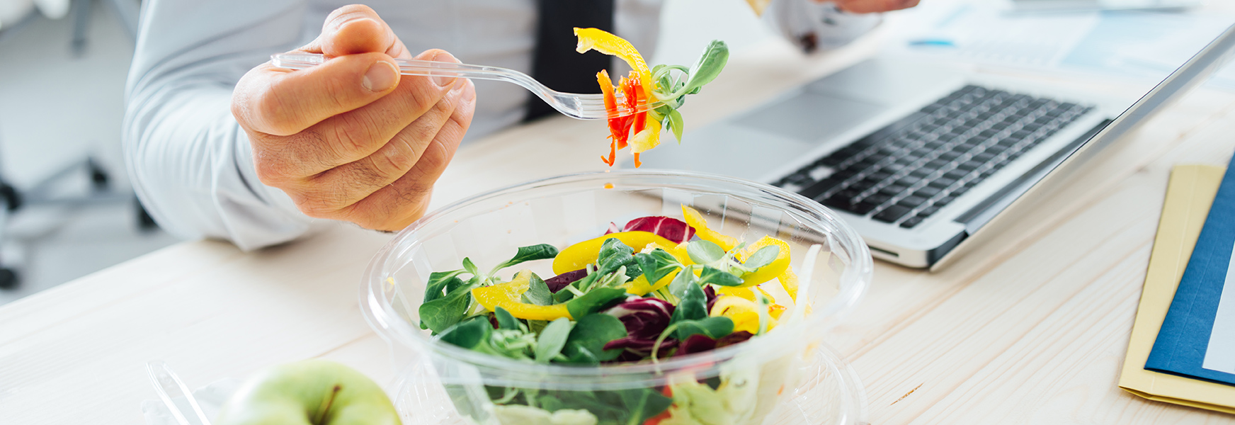 Employee eating healthy salad at desk