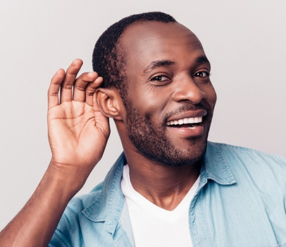 man with hand at ear listening