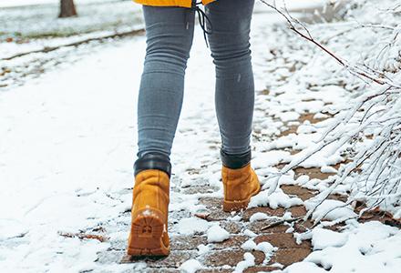 Woman wearing boots walking along snowy brick path
