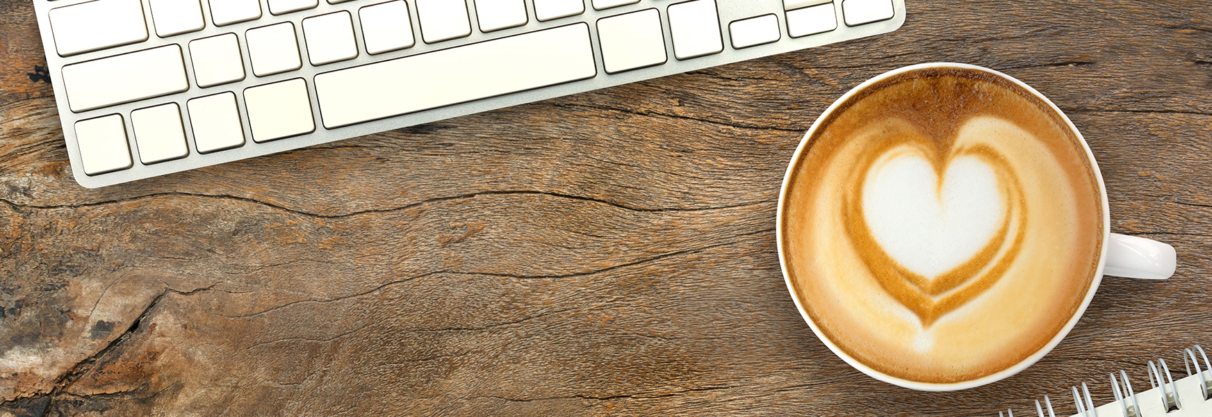 Latte with heart-shaped foam on desk with keyboard and notebook