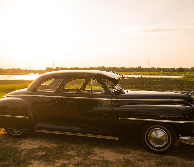 Vintage Automobile In Green Field At Dusk