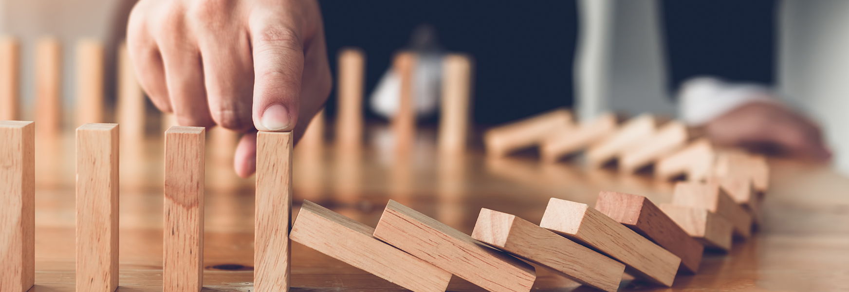 Man with finger on falling dominoes