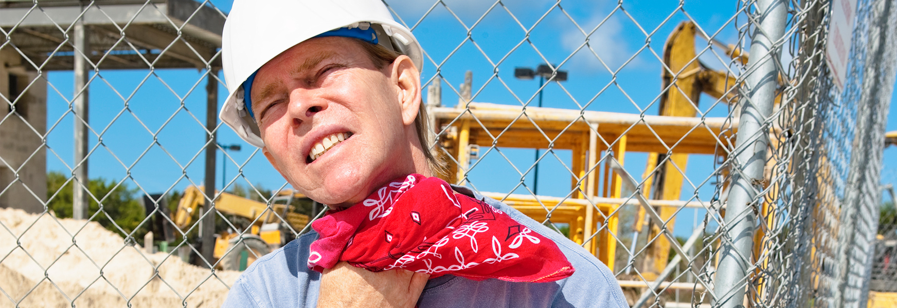 Man working in sun wiping sweat from neck with a bandanna