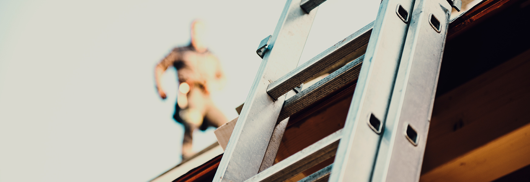 Ladder leaning on a building, out of focus worker walks on roof in background