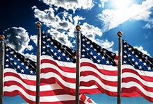 Four american flags blowing in the wind against a summer blue sky background