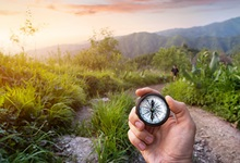 Hand holding a compass with out of focus mountains, tropical vegetation, and hiking partner in background