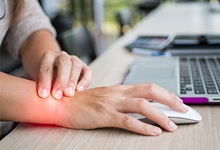 Woman using computer mouse grasping sore wrist
