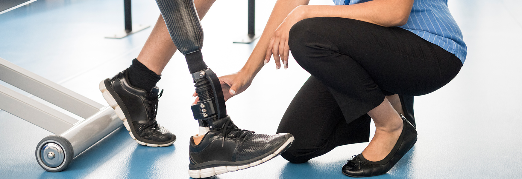 Medical professional assists patient with prosthetic leg