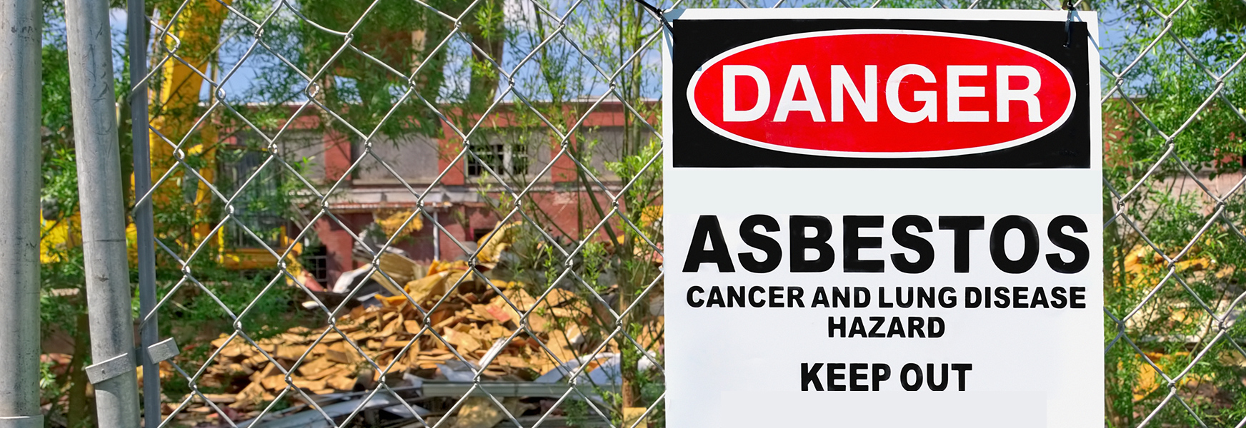 asbestos danger sign hung on fence in front of old building being demolished