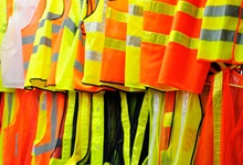 Orange and yellow safety vests hanging on a rack