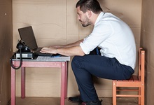 Man sits at a computer in a makeshift cubicle made out of cardboard