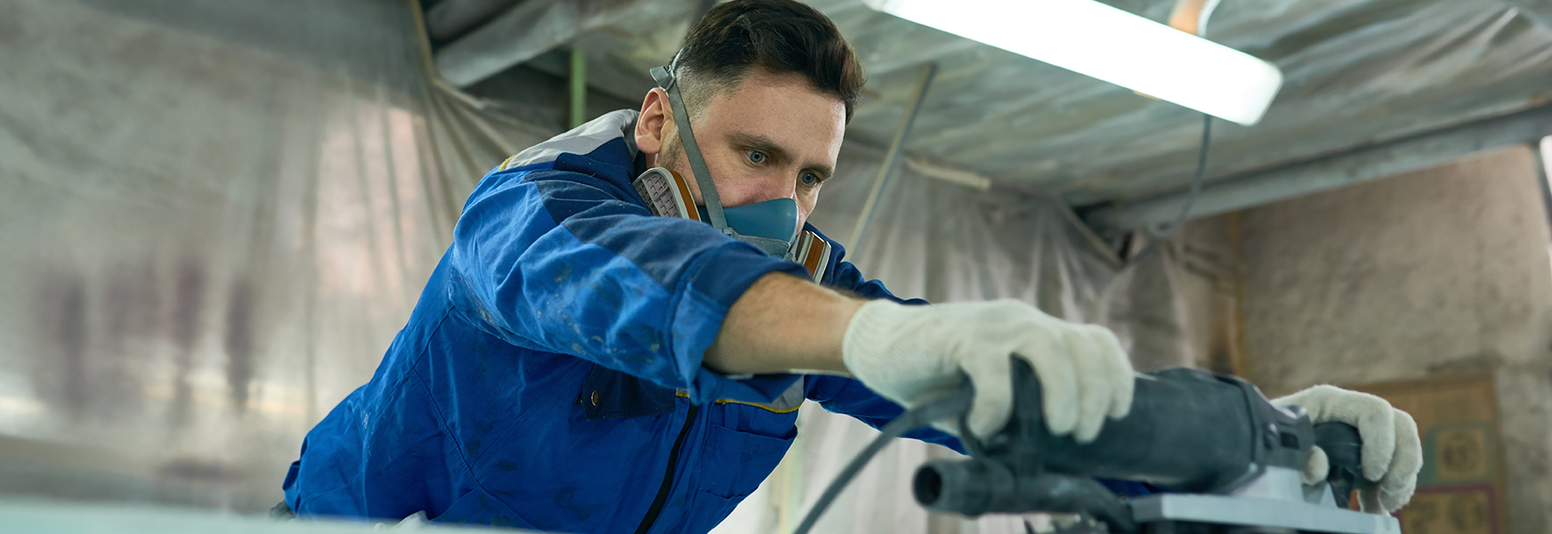 Man in respirator using a power sander