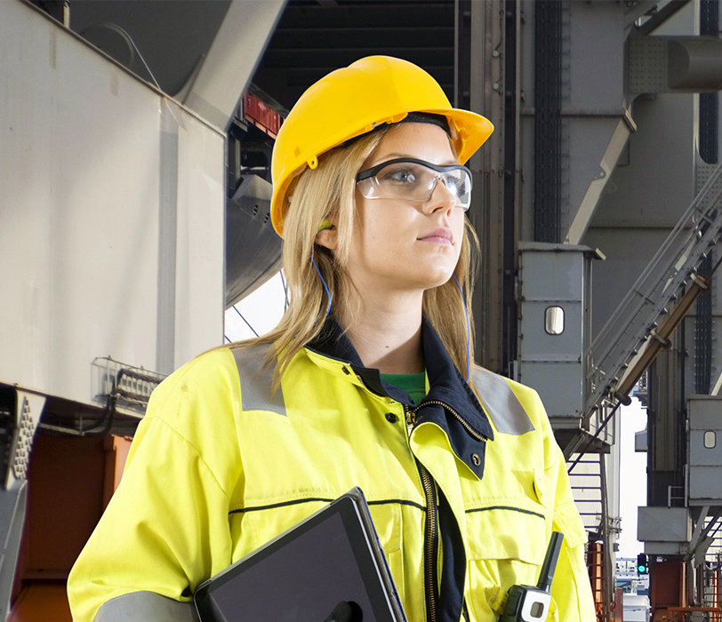 Woman wearing hard hat and personal protective equipment standing in a factory