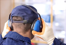 Factory worker applying ear protection