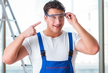 Young male worker pointing at safety glasses worn on his face.