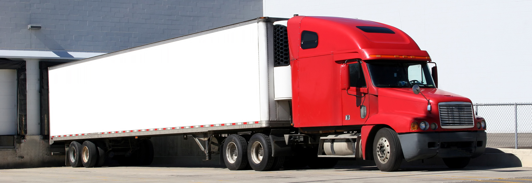 A semi truck sits parked at a loading dock