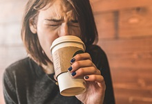 Woman sipping hot coffee and burning her mouth
