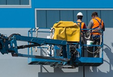 Two workers working in a boom lift.