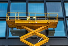 Workers in elevated work platform cleaning windows