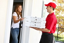 Woman greeting pizza delivery driver at front door.