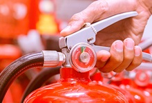 Hand holding a fire extinguisher