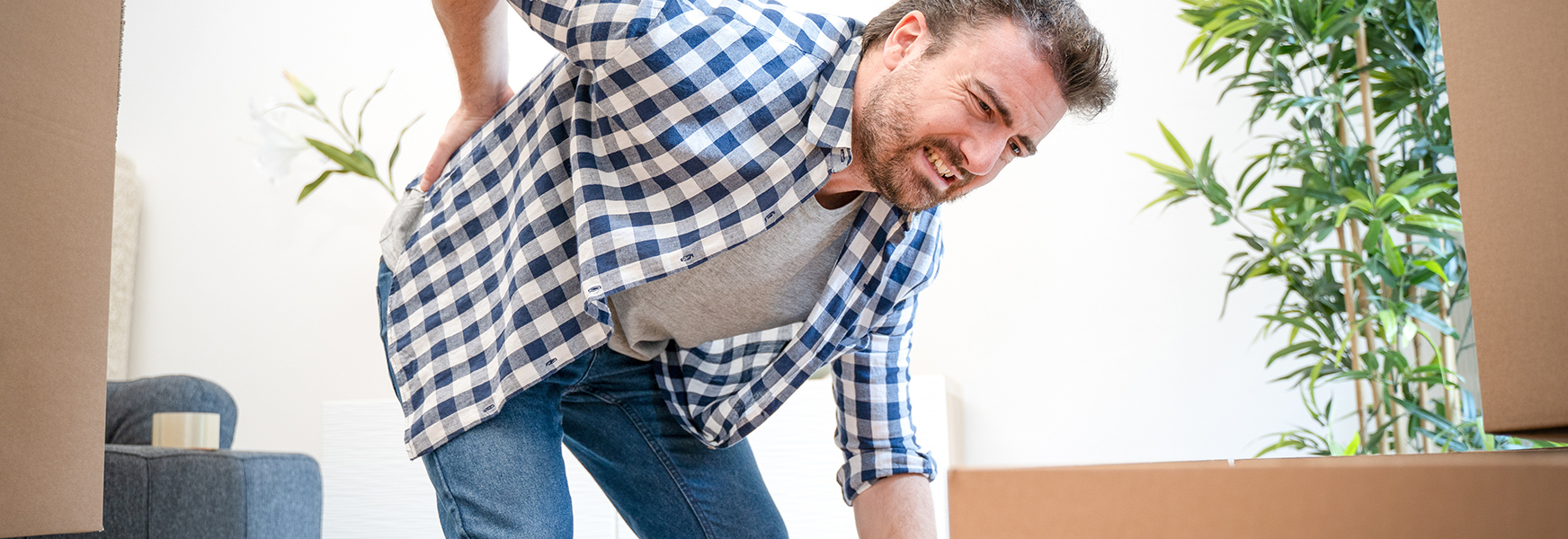 Man with sore back from improper lifting technique