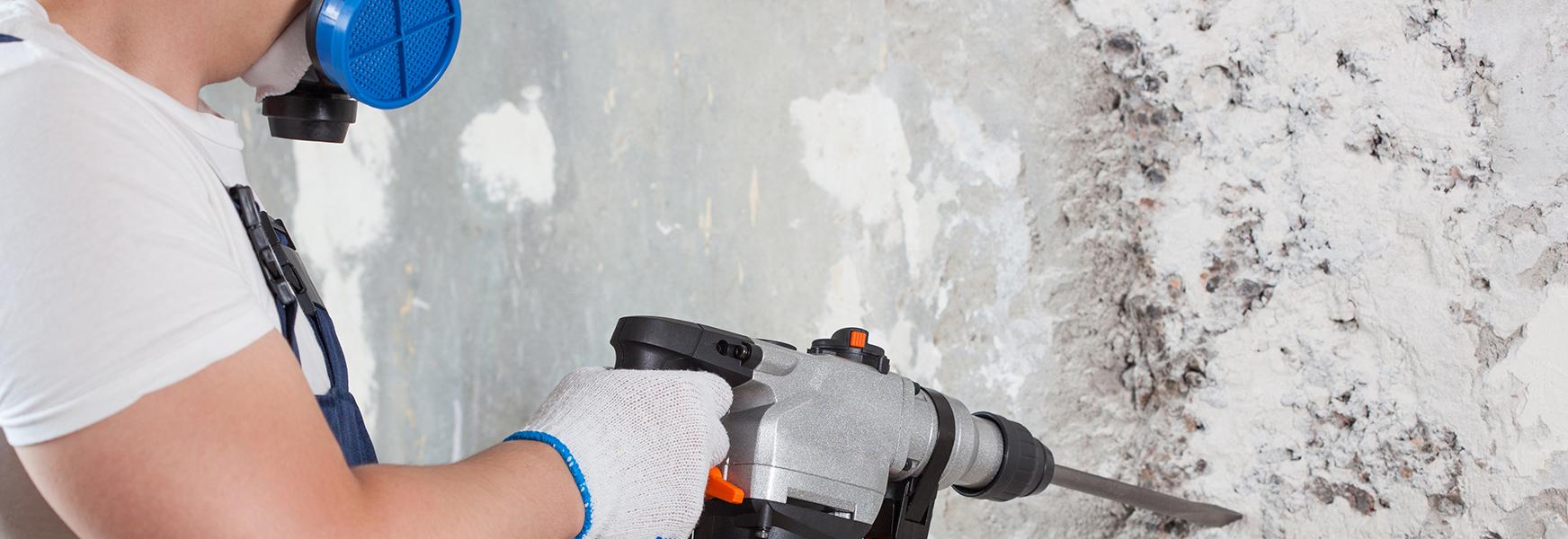 Worker wearing respirator doing wall construction