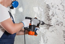 Worker wearing respirator doing wall construction