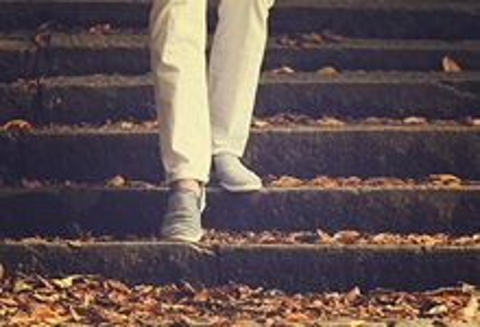 Legs walking down leaf-covered stone steps