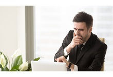 Office worker using computer and yawning at desk.
