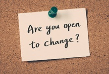 """""""Are you open to change?"""" sticky note pinned to corkboard."""
