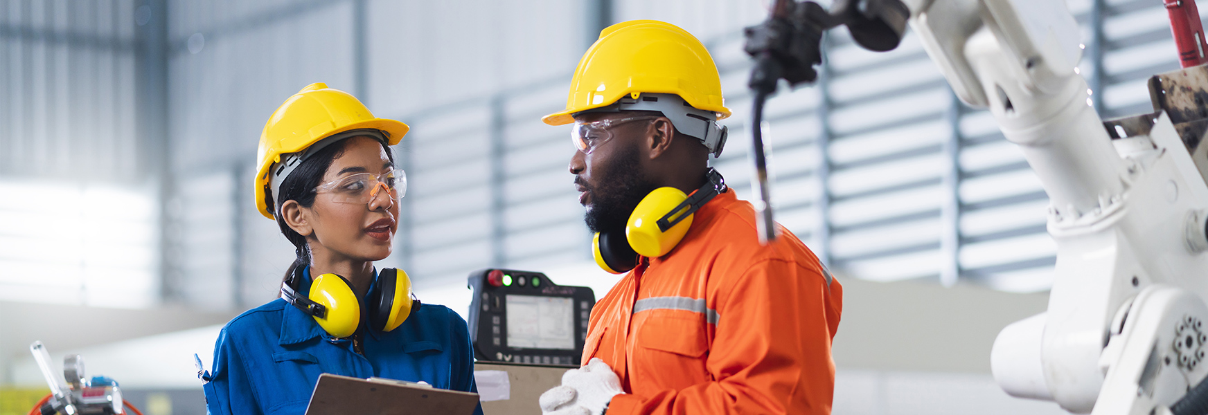 Workers wearing safety equipment having a conversation on factory production floor