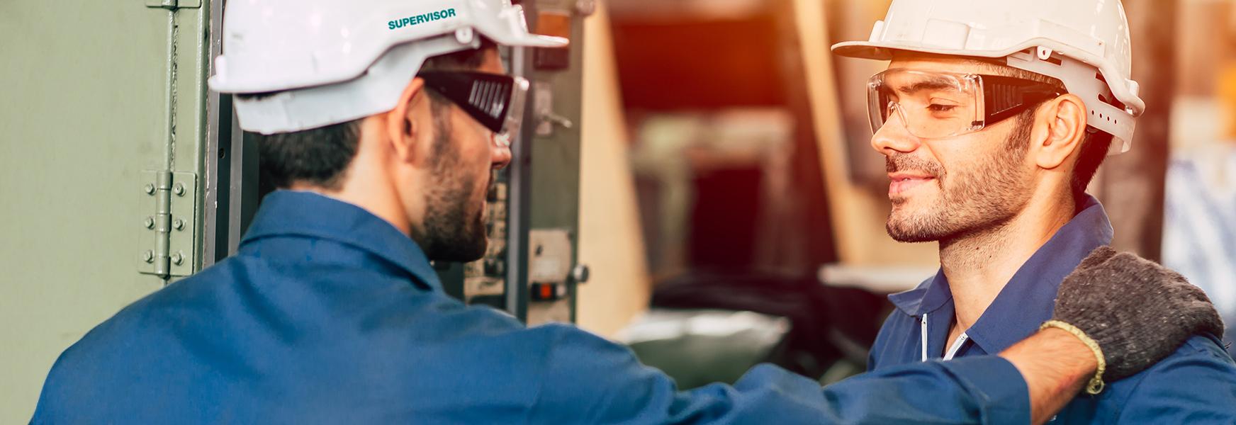 Supervisor praising worker in factory