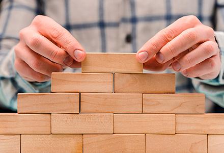 Hands stacking wooden blocks