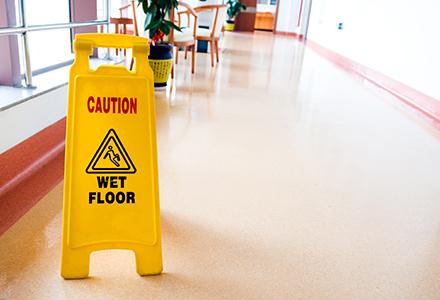 Wet floor sign standing in business hallway