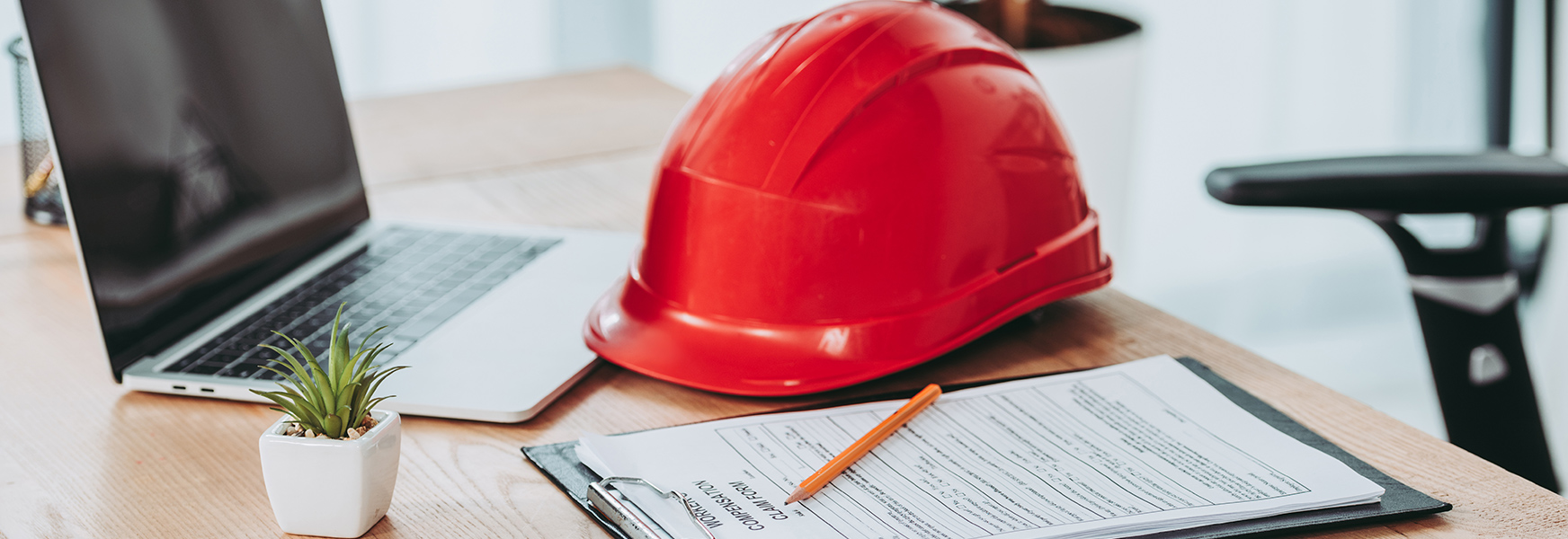 Hardhat and office supplies laying on office desk