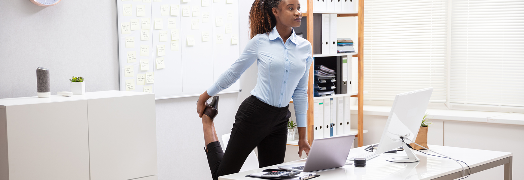Young Businesswoman Doing Leg Stretches at Desk