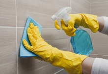 Gloved hands cleaning tile