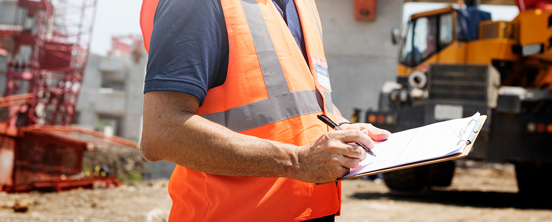 man on construction site with safety checklist