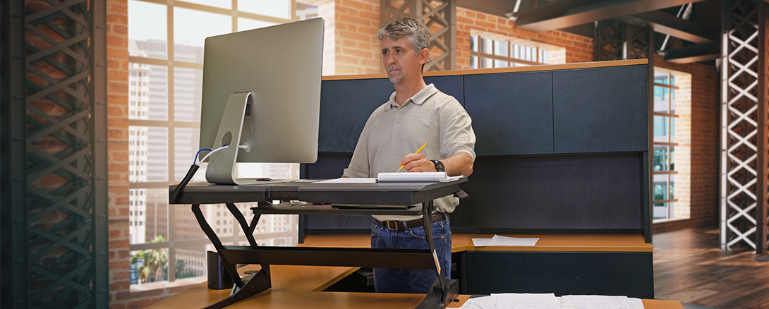 worker at sit/stand ergonomic workstation