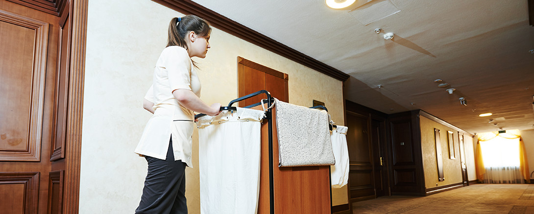 hotel housekeeper pushing cleaning cart down hallway