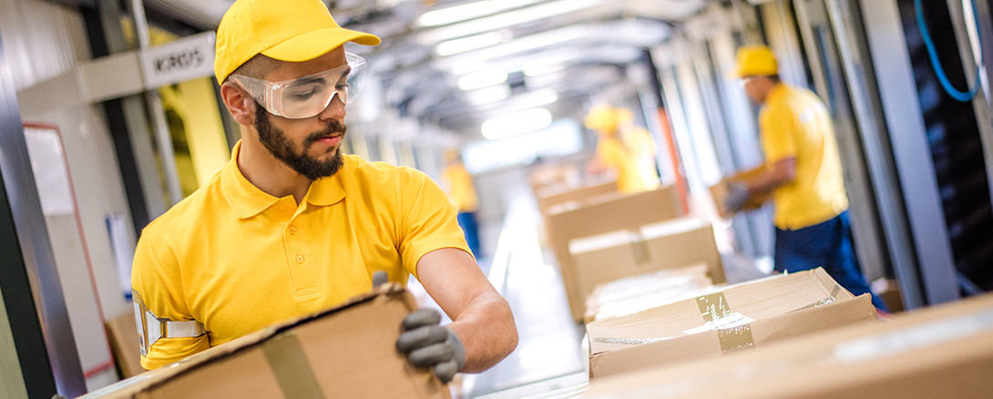 worker in safety glasses working at warehouse distribution facility
