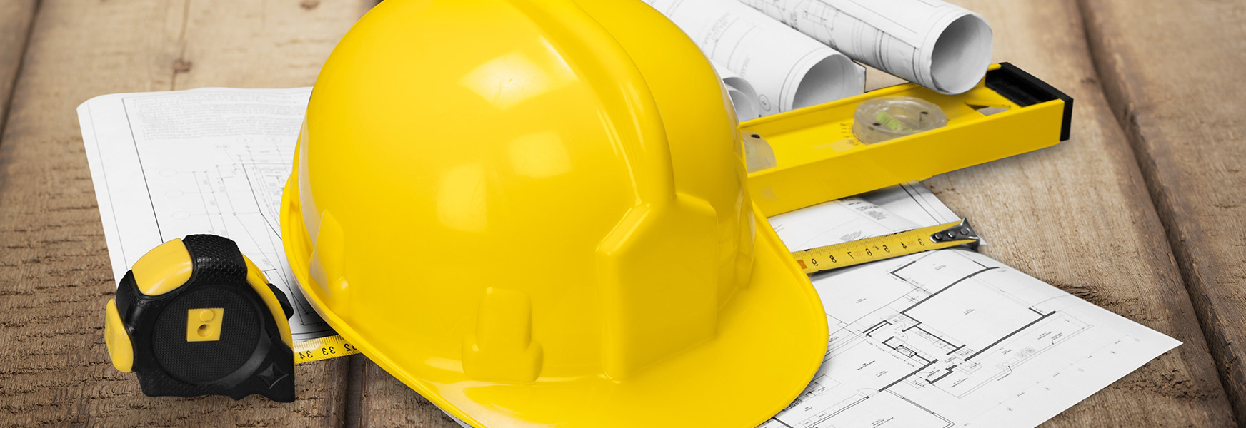 construction hard hat, building plans and tape measurer