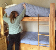 Housekeeper lifting mattress on top bunk
