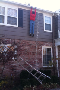 Man hanging onto the edge of a roof after his ladder falls.