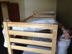 Two housekeepers making top bunk bed