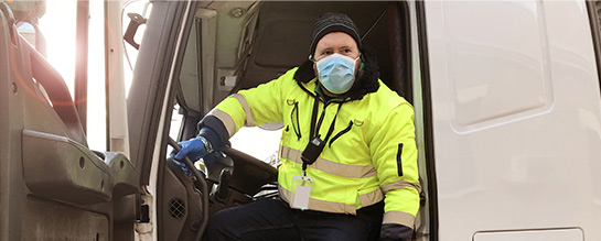 Delivery driver wearing masks and gloves in a box truck